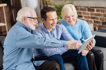 Childlike curiosity. Pleasant elderly couple sitting on the couch next to their son and asking him questions about how to use a tablet, pointing at it