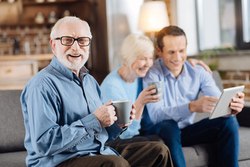 Cozy weekend. Upbeat elderly man posing with a coffee cup and smiling at the camera while his wife and son using a tablet together in the background