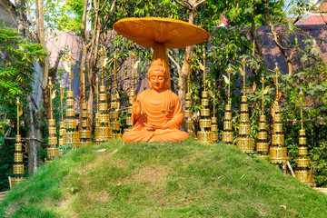 orange buddha with golden bells, chiang mai. thailand.
