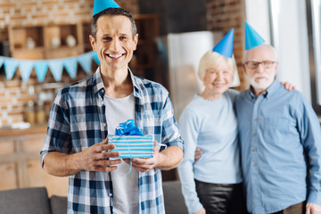 Happy birthday man. Pleasant elderly man posing with his birthday present while his elderly parents hugging in the background, and all of them wearing blue party hats