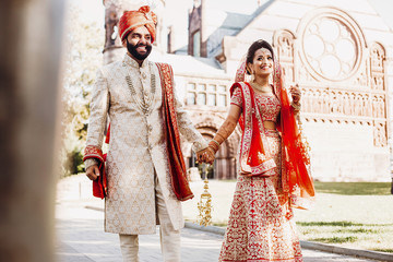 Indian groom dressed in white Sherwani and red hat stands with stunning bride in red lehenga walk outside