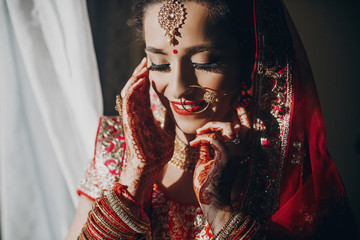 Stunning Indian bride dressed in Hindu red traditional wedding clothes lehenga embroidered with gold and a veil smiles tender hiding her face