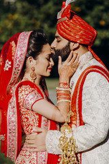 Indian groom dressed in white Sherwani and red hat with stunning bride in red lehenga stand and hold each other tender while kissing
