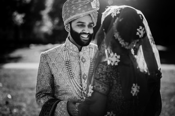Black and white picture of gorgeous Indian newlyweds dressed in traditional sherwani, lehenga pose outside