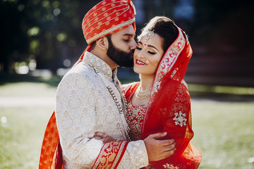 Indian groom dressed in white Sherwani and red hat with stunning bride in red lehenga stand and hold each other tender
