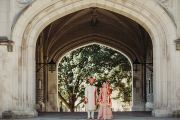 Indian groom dressed in white Sherwani and red hat with stunning bride in red lehenga stand and hold each hands posing before a Hindu temple
