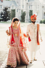 Indian groom dressed in white Sherwani and red hat with stunning bride in red lehenga stand and hold each hands walking outside