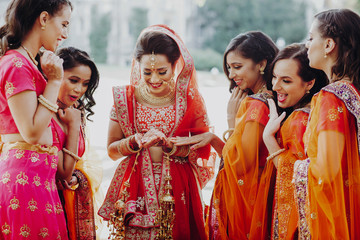 Pretty Hindu bridesmaids surround stunning Indian bride in red lehenga embroidered with gold while she looks at her wedding ring