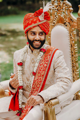 Handsome bearded Indian groom in white sherwani and red hat sits on the chair during the Hindu wedding ceremony