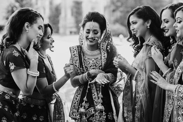 Pretty Hindu bridesmaids surround stunning Indian bride in lehenga embroidered with gold while she looks at her wedding ring