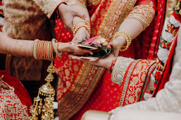 Tender hands of an Indian bride covered with henna tattoo hold groom's hands during the Septapadi ceremony