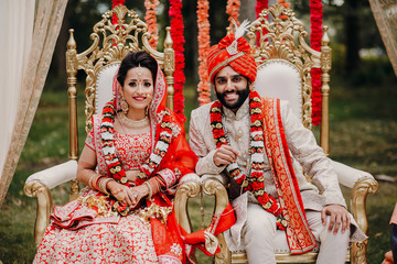Indian bride and groom dressed in traditional shewrani, lehenga and with flower garlands on their necks sit on the chairs during Hindu wedding ceremony