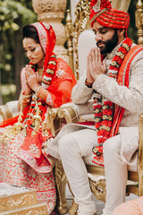 Indian bride and groom dressed in traditional shewrani, lehenga and with flower garlands on their necks sit on the chairs and pray during Hindu wedding ceremony