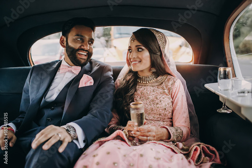 97e72067c8 Handsome Indian groom dressed in traditional black suit and pretty bride in  pink wedding dress with golden embroidery sit inside the car