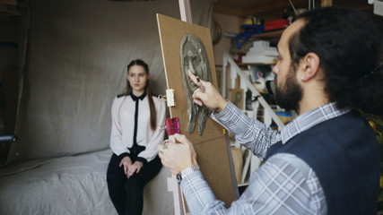 Skilled sculptor works with plasticine on canvas to create woman's face of posing model in art studio