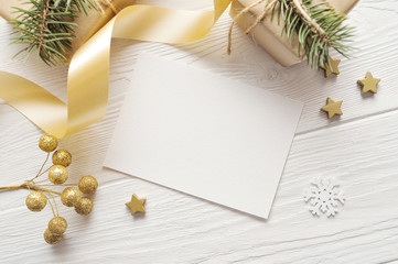 Mockup Christmas greeting card top view and gold star, flatlay on a white wooden background with a ribbon, with place for your text