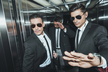 bodyguard stopping paparazzi when celebrity standing in elevator