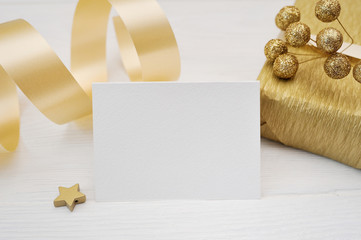 Mockup Christmas greeting card with gold gift ribbon, flatlay on a white wooden background, with place for your text