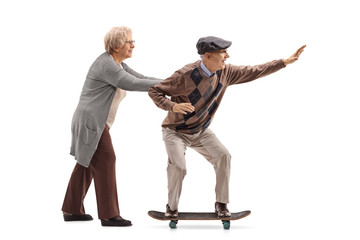 Elderly woman pushing an elderly man on a skateboard