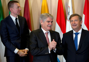 Spanish Foreign Minister Alfonso Dastis Quecedo speaks with Slovenian Foreign Minister Karl Erjavec during a group photo in Brussels