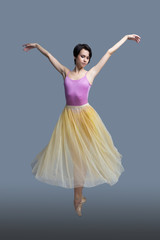 ballerina is dancing in the studio on a gray background