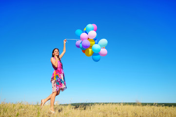 Beautiful, cheerful young woman in a bright dress with colorful balloons  on a field with a blue sky in the summer. Warm sunny summer day with light breeze.