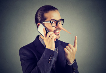 Sly liar business man with long nose talking on mobile phone isolated on gray wall background.