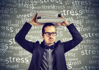 Stressed doomed business man standing with heavy folders on his head isolated on gray background