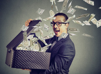 Excited successful man opening a box with money flying out away