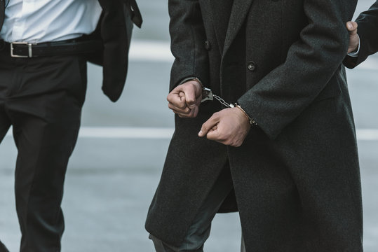 Cropped image of security guard holding man in handcuffs