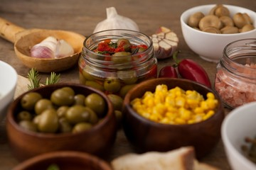 Olives and corns in bowl by spices