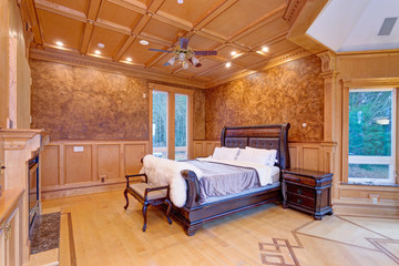Welcoming mansion bedroom with a rustic wood coffered ceiling