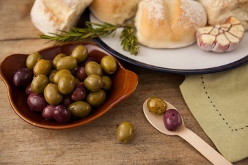 High angle view of olives in plate by bread