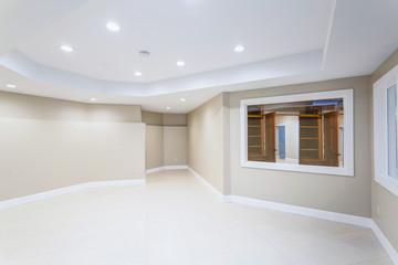 Light Empty basement room with beige tiled floor.