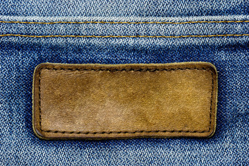 Blank brown leather label on vintage blue jeans. Suitable for backgrounds, articles about fashion clothing.