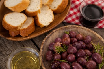 Olives and bread with oil on table