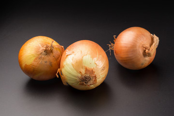 Fresh golden onions isolated on a black background