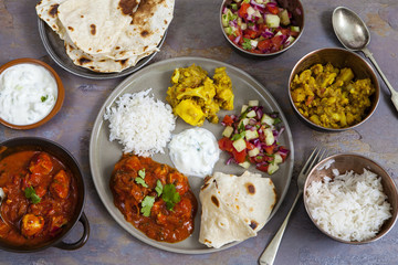 Chicken tikka masala with aloo gobi, rice, flat breads and salad