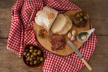 Overhead view of bread and olives with meat on napkin