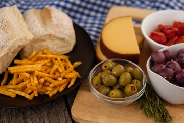 French fries with bread by olives and vegetables on cutting