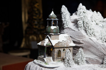 christmas, decoration from ceramics, toy orthodox church chapel in the snow near rocks and trees