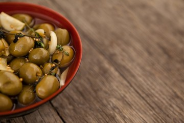 Cropped image of olives with garlic and oil in bowl