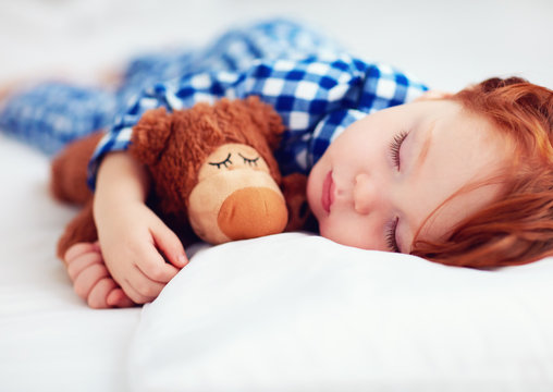 adorable redhead toddler baby in flannel pajamas sleeping with plush warmer toy