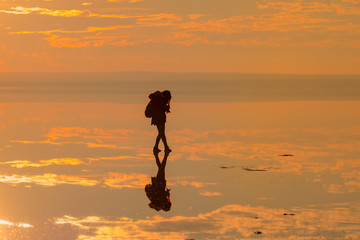 Silhouette of alone woman takes a picture of a sunset reflected in waters of salt lake, Ankara