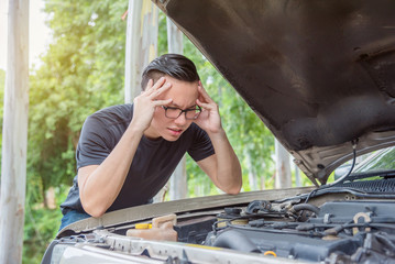 Young asian man with stress face waiting for assistance with his broken car