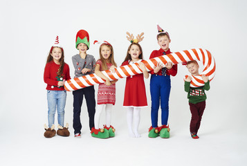 Children with artificial candy cane .