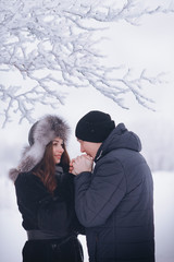A loving couple on a winter walk. Snow love story, winter magic. Man and woman on the frosty street. The guy and the girl are resting on the snow. Christmas mood of a young family.