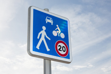 road sign indicates the speed limit and the sharing of the road between pedestrian bike and cars