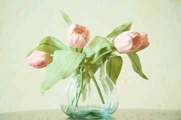 tulips in a glass jug on a metal table on a light background