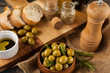 High angle view of olives by pepper shaker and cutting board